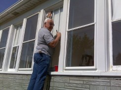 John Clark helps repair and weatherize windows for a needy family in Racine, Wis.