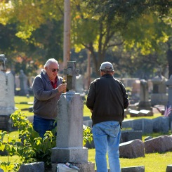 John Clark and John Murphy repair a vandalized cross at Old Holy Cross Cemetery.