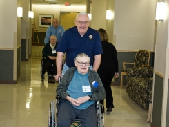 John Clark wheels a veteran to a Christmas party at the state veterans home in Union Grove, Wis.